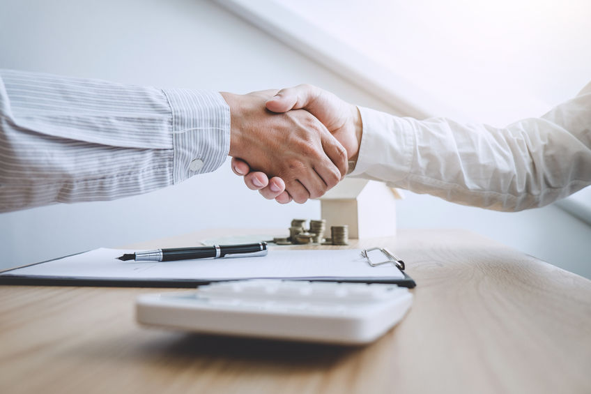insurance agent and client shaking hands over table